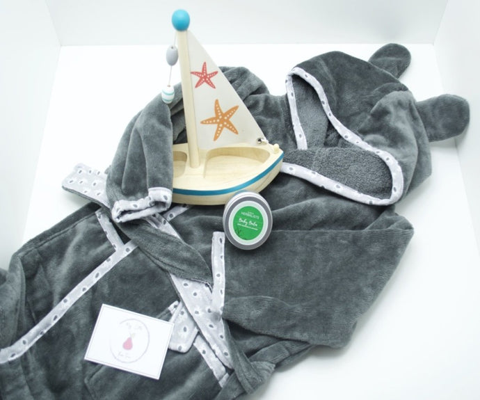 A dark grey bathrobe with ears on the hood and a light grey trim with an elephant pattern, also a grey elephant shaped silicone teether, a small wooden sail boat with an orange starfish and red starfish on the sail and a silver tin of baby balm with a green and white sticker.