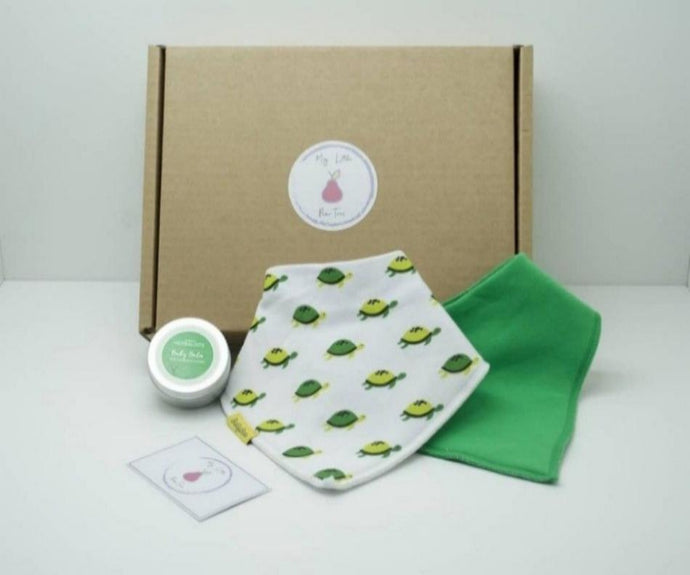 Natural coloured gift box with the My Little Pear Tree logo circular sticker on the lid, the sticker has a purple boarder with a pink pear in the centre with the writing My little Pear Tree, a white  bandana style bib with green and yellow turtle pattern, a plain green bandana bib, a silver tin of baby balm with a green label on the lid and a My Little Pear Tree card.