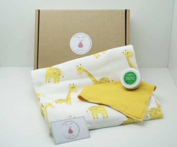 Natural coloured gift box with the My Little Pear Tree logo circular sticker on the lid, the sticker has a purple boarder with a pink pear in the centre with the writing My little Pear Tree, a yellow bandana style bib, a white muslin cloth with yellow giraffe pattern, a silver tin of baby calm with a green label on the lid and a My Little Pear Tree card.