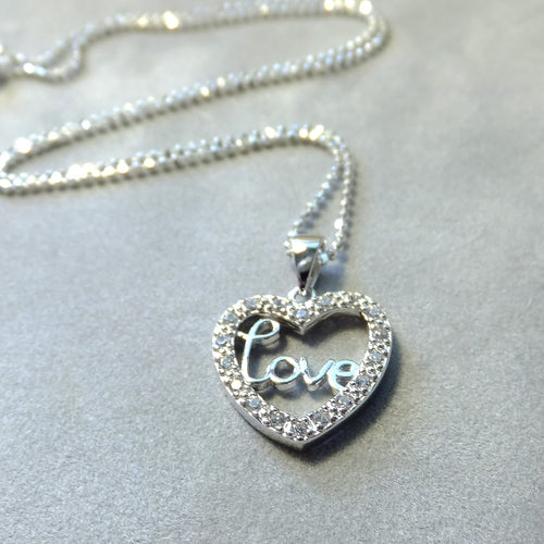 Crystal heart pendant that says love in sterling silver