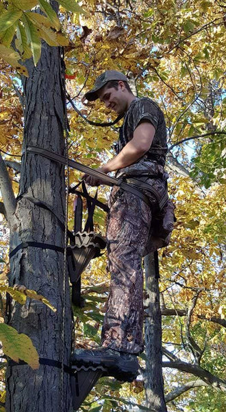 Man standing on stealth step tree ladder stand.