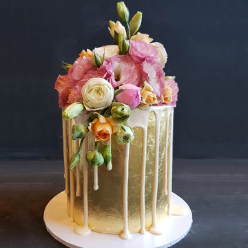 Elegant 23ct gold cake with white drip and fresh florals