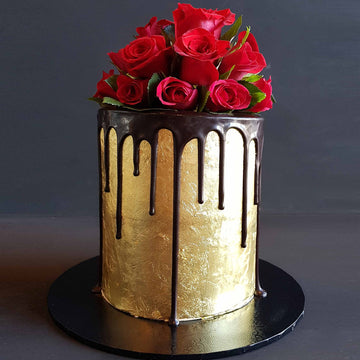 Elegant 23ct gold cake with dark chocolate drip and fresh red roses