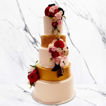 Fondant covered wedding cake with gold shimmer spray