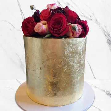 Gold luxury wedding cake topped with fresh floral