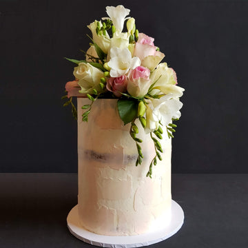 Naked look buttercream cake with smudges of pale pink and fresh florals