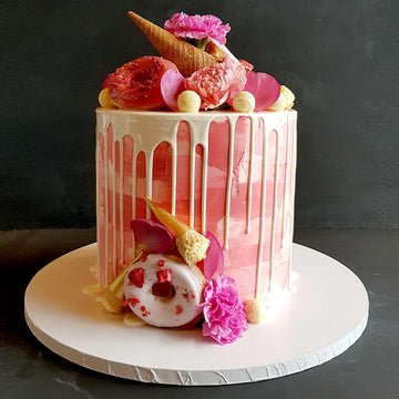 Pink buttercream cake with white chocolate drip, donuts and waffle cones