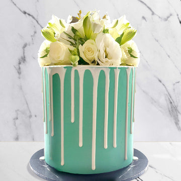 Tiffany blue cake with chocolate drip and fresh white florals