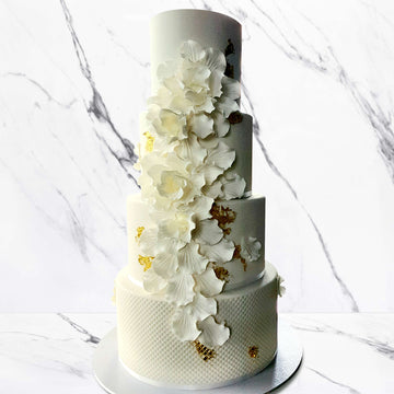 Fondant covered cake 4 tier flower detail gold leaf