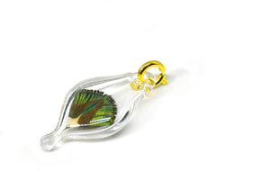 small blown glass charm with a cruelty-free iridescent peacock feather inside