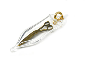 Glass capsule charm with antique brass scissors inside glass