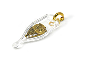 Glass capsule charm with antique brass owl inside glass. Approx 1 1/2 inches long by 3/4 inch wide