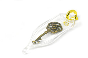 Glass capsule charm with antique brass key inside glass