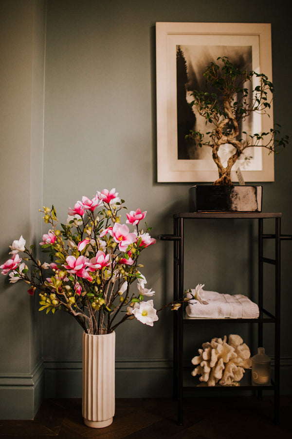 Realistic faux flower arrangement of white and pink flowering Magnolia branches with vivid green foliage delivered in an elegant, ridged, matt white vase.