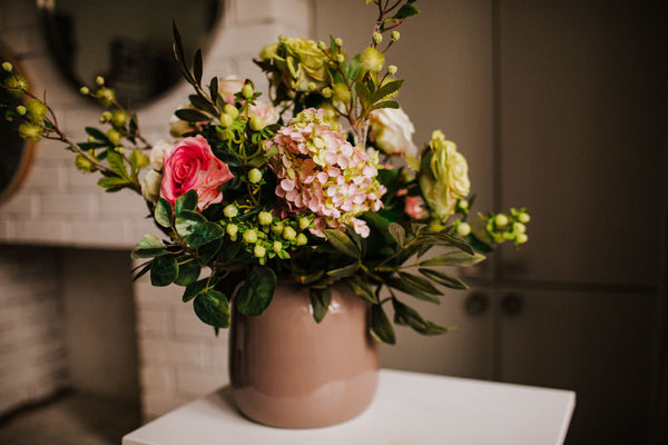 Realistic Faux flower arrangement of large roses, pink hydrangeas, Agapanthus and seasonal foliage and berries in an elegant taupe and gold accent vase to by for the home or to gift.