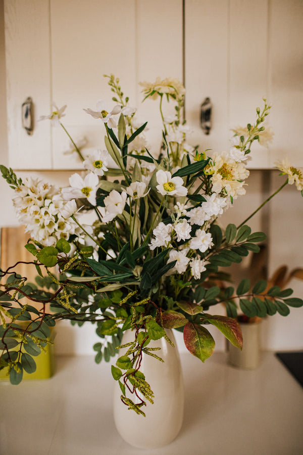 Realistic faux flower arrangement of fresh white blooms and greenery including Campanula, Cosmos and Scabious delivered in an elegant taupe and gold accent vase.