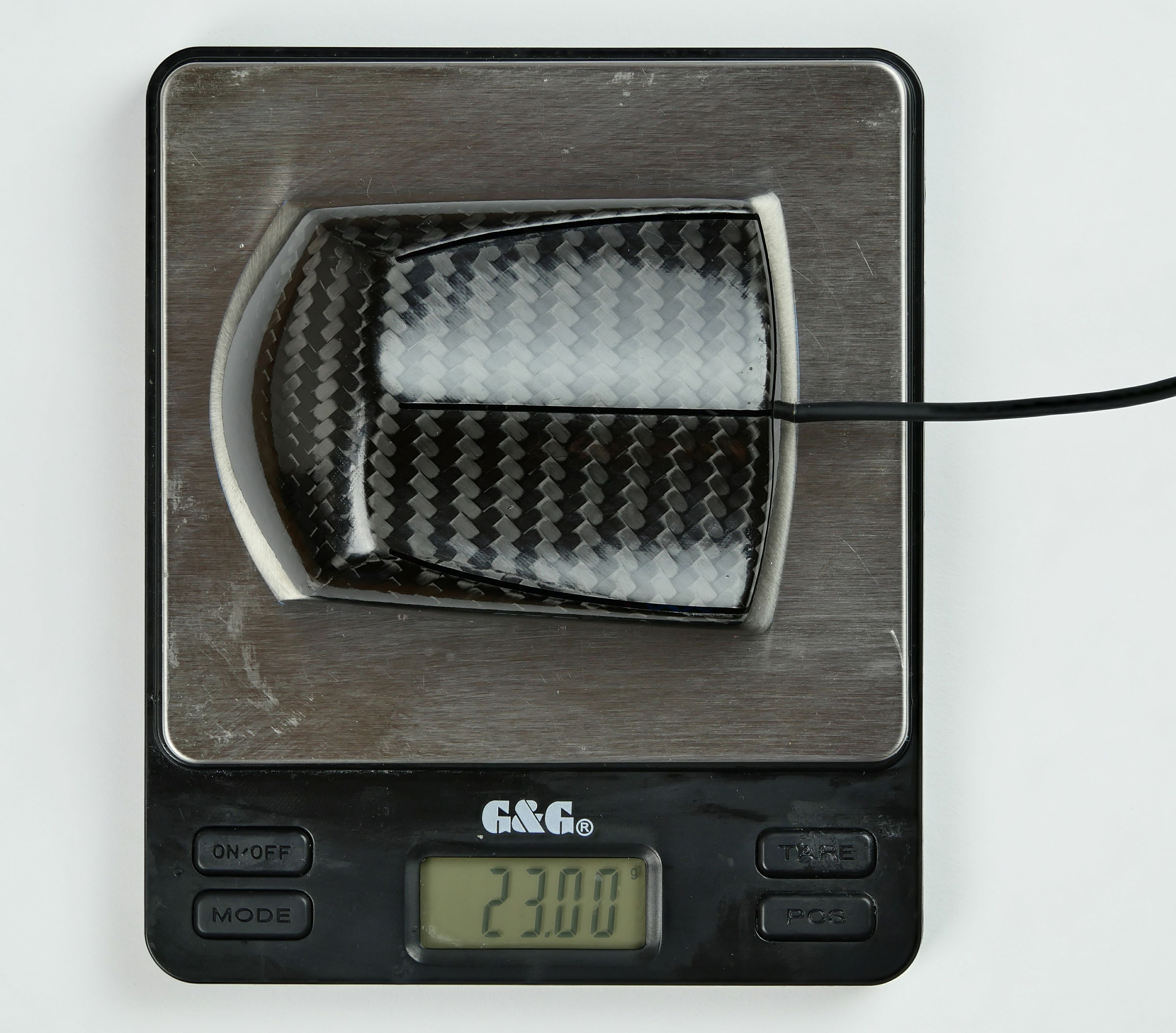 This picture shows the Zaunkoenig M1K sitting on a scale. The M1K weighs in at just 23 grams, easily making it the worlds lightest gaming mouse. The only gaming mouse that can hold a candle to the M1K is the M2K, which is just one gram heavier, clocking in at 24 grams.