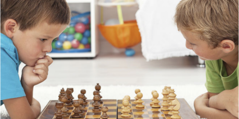 Two young boys playing chess game together