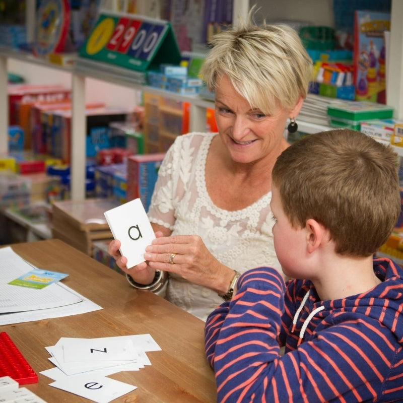 Blonde lady sitting at desk with young boy teaching him how to write name