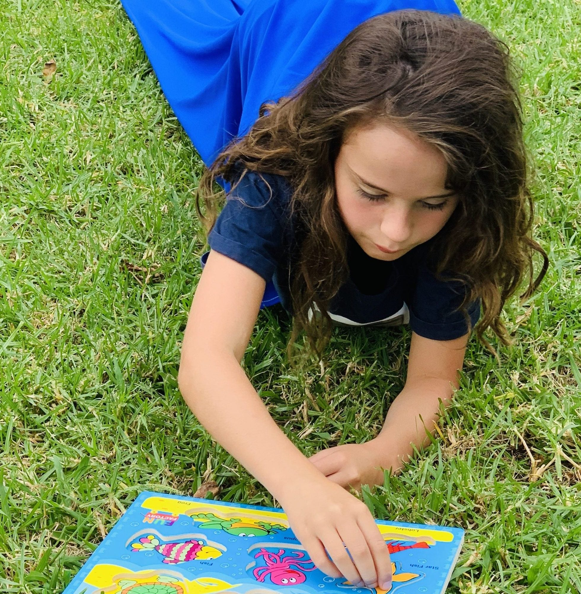 Girl lying on grass inside blue Lycra Tunnel playing game