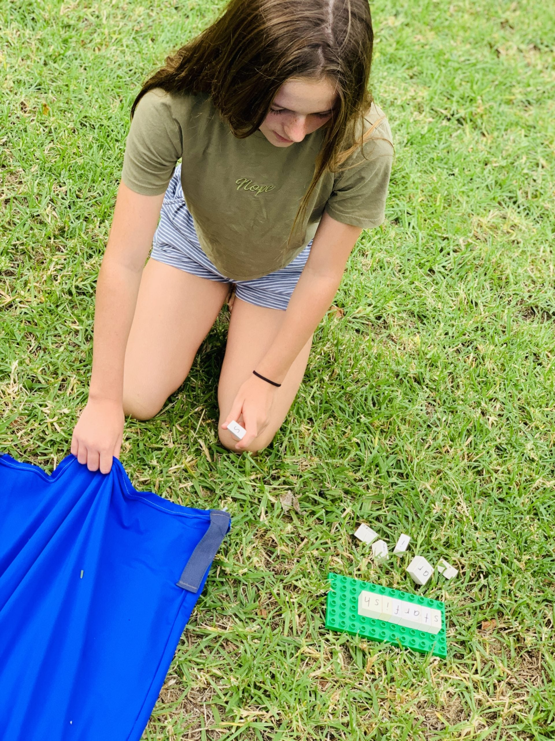 Girl kneeling down on grass with blue lycra tunnel in hand