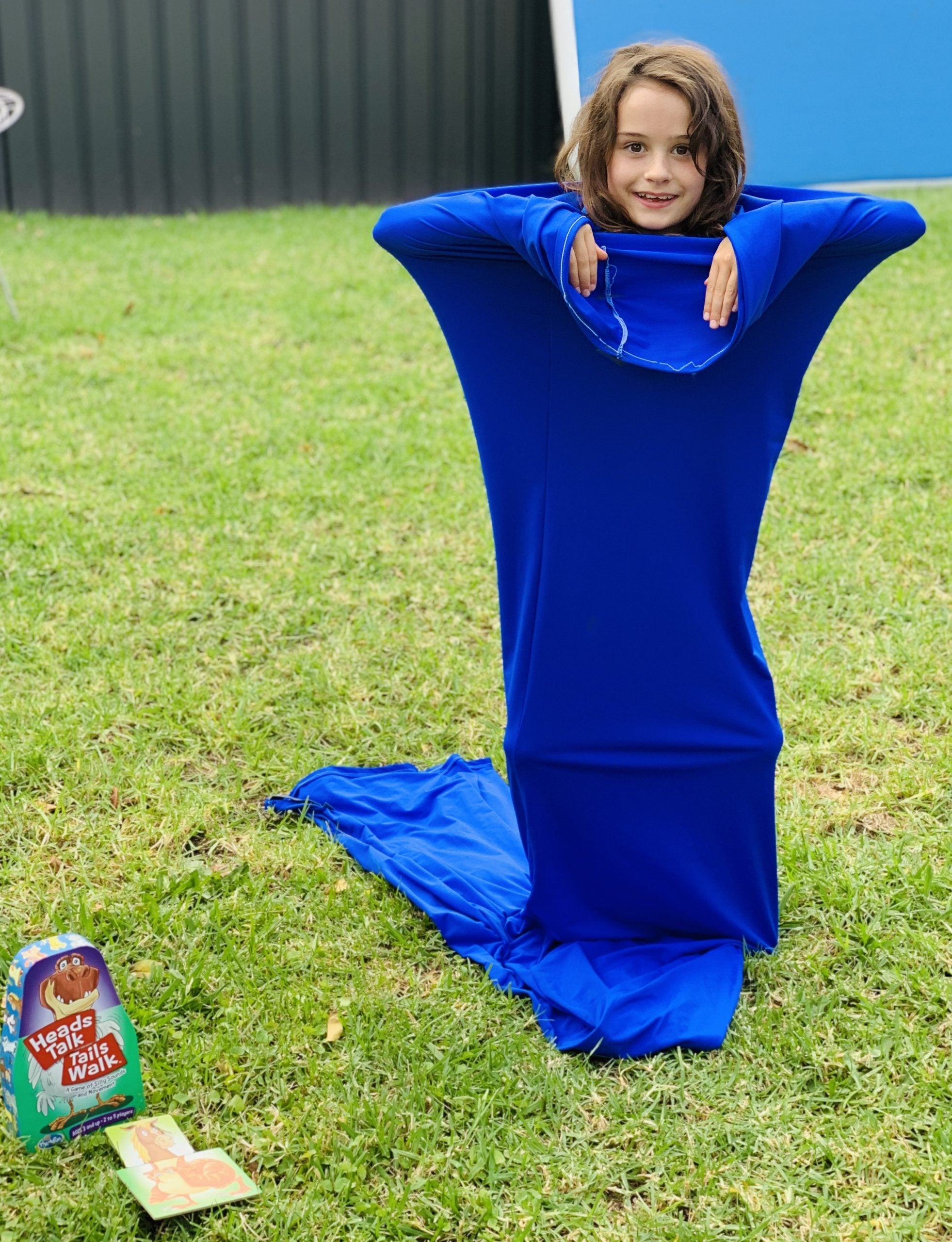 Girl standing on grass inside blue Lycra Tunnel playing game