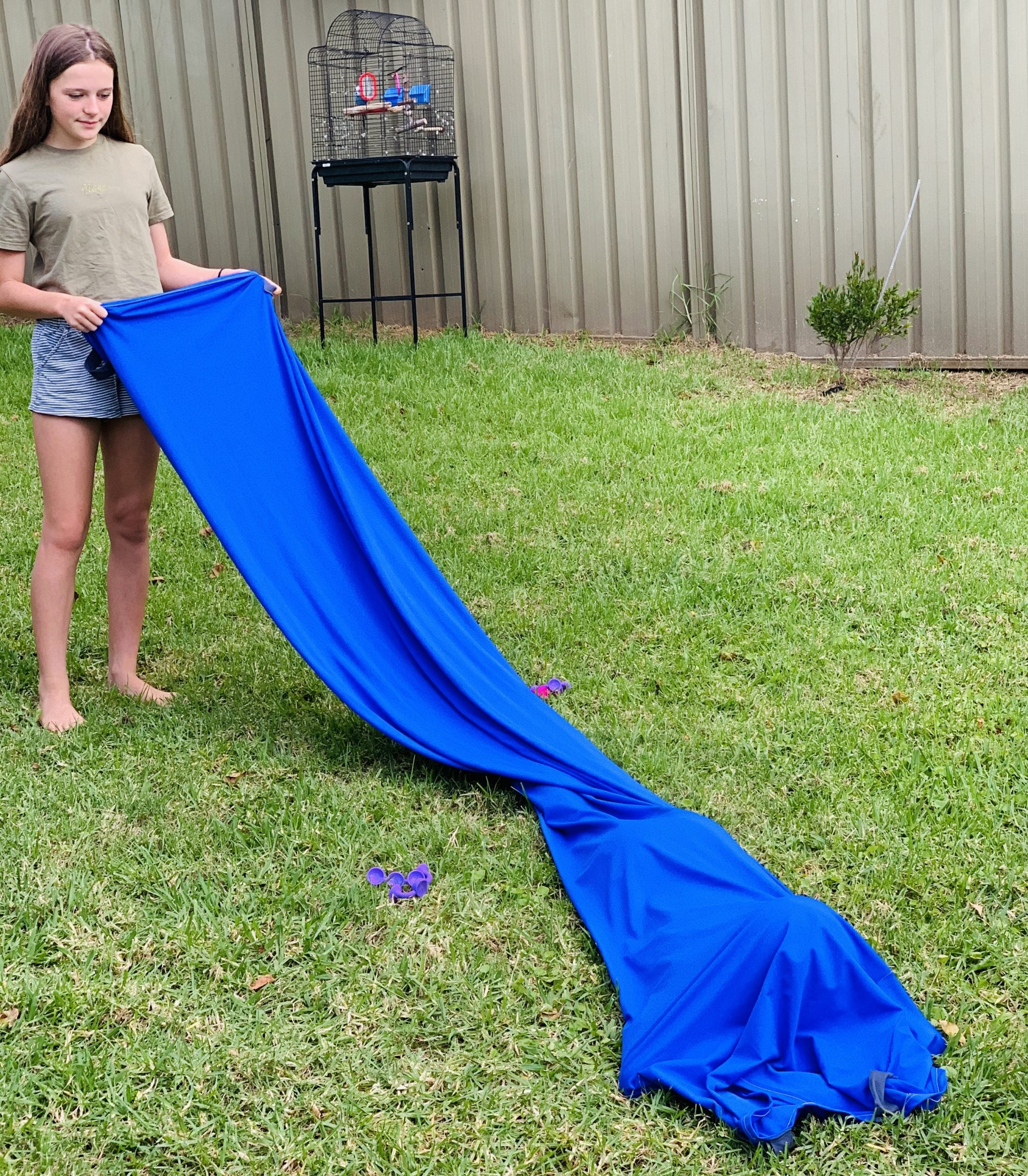 Girl standing on grass holding stretched out blue lycra tunnel