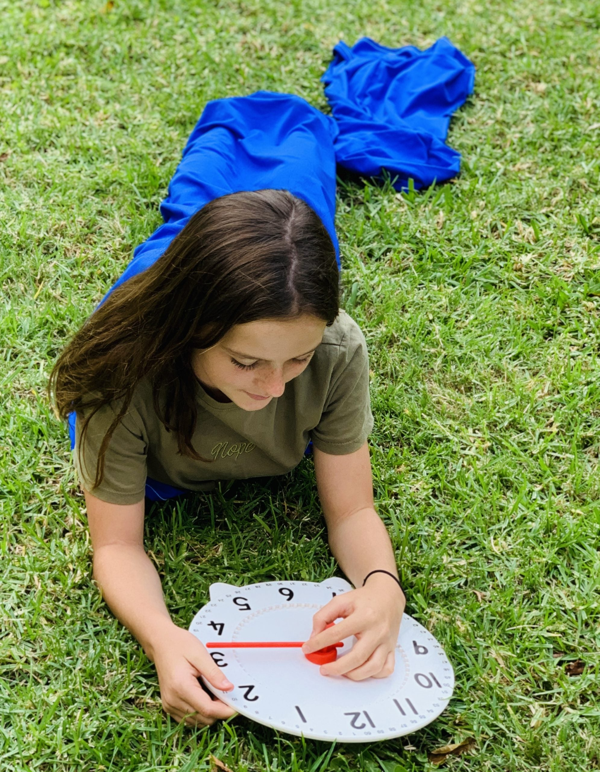 Girl lying on grass inside blue Lycra Tunnel playing with clock