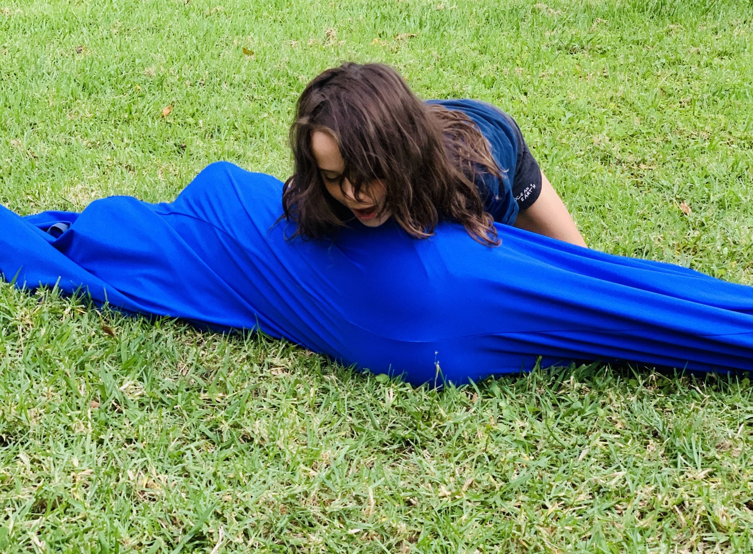 Girl on grass trying to roll blue Lycra Tunnel