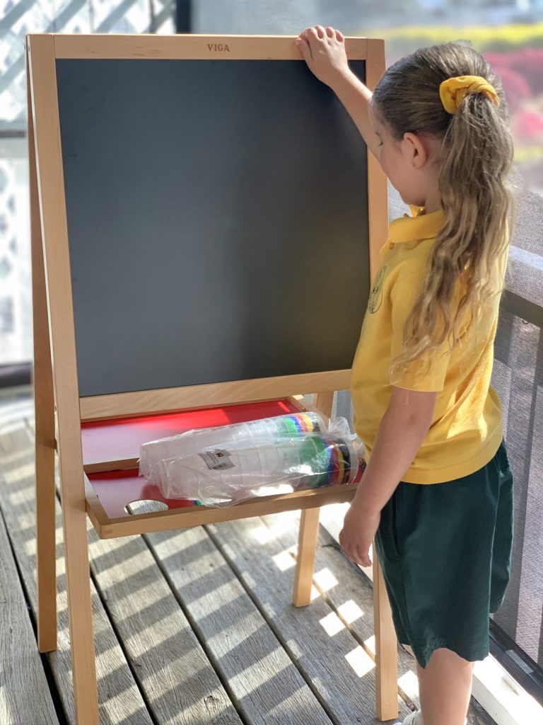 Young girl in yellow shirt learning to write their name with a Standing Easel