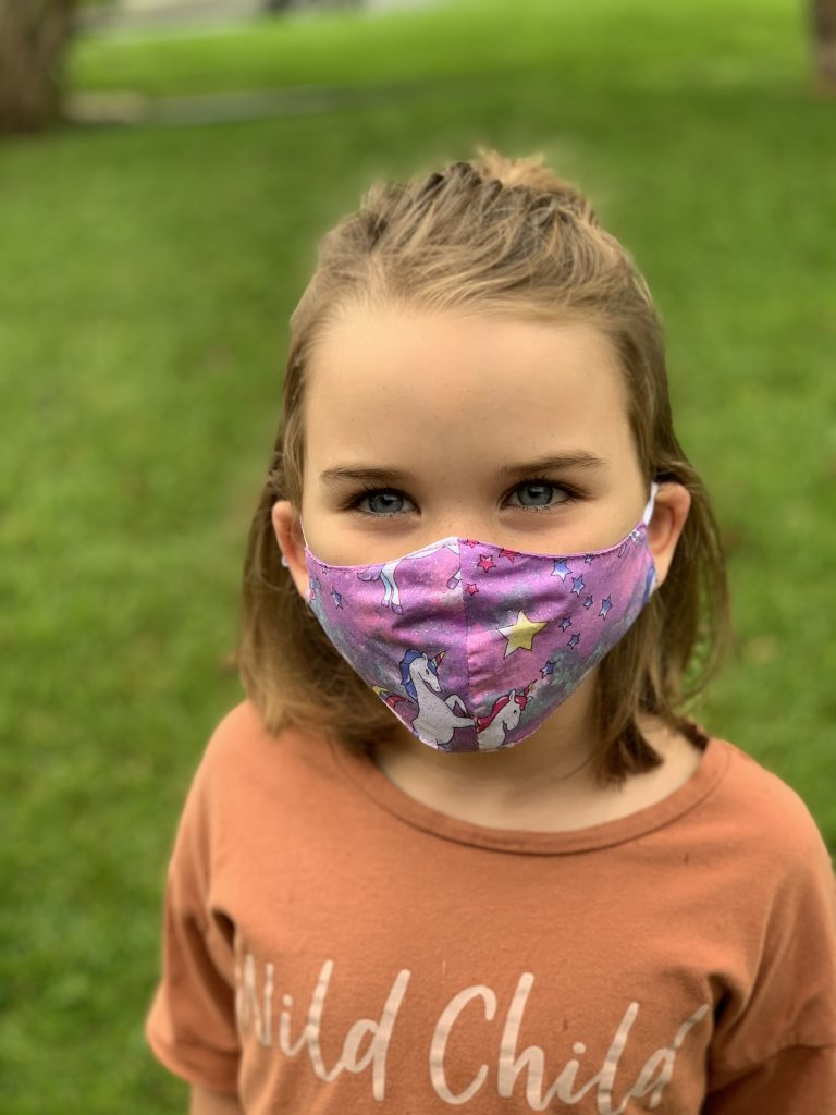 Little girl wearing a face mask that has unicorns on it
