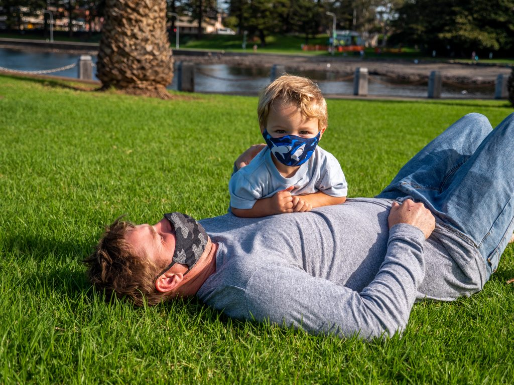 Father laying down on the grass playing with his son whilst both of them are wearing face masks