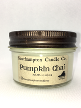 Load image into Gallery viewer, A creamy off-white natural soy and coconut wax candle in a glass mason jar. It has a bronze lid and a kraft paper label that reads 'Southampton Candle Company' and 'Pumpkin Chai'. Its net weight is 2.3 ounces.