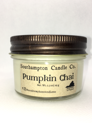 A creamy off-white natural soy and coconut wax candle in a glass mason jar. It has a bronze lid and a kraft paper label that reads 'Southampton Candle Company' and 'Pumpkin Chai'. Its net weight is 2.3 ounces.