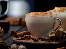 Load image into Gallery viewer, A hot chai latte on a wooden platform, surrounded by cinnamon sticks, nutmeg, and clove.