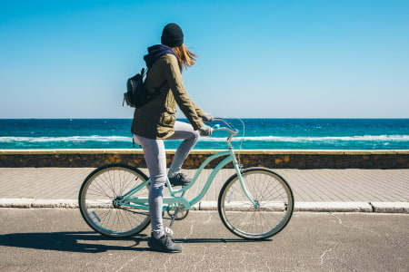 This is a picture of a beach cruiser bike rider at the beach.