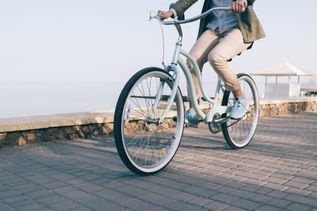 This is a picture of a bike rider on a beach cruiser.