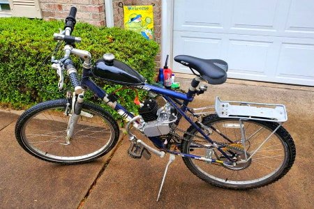 Black and silver customized 2-stroke engine installed on bicycle.