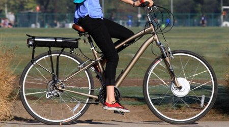 Person riding bicycle with e-bike kit.