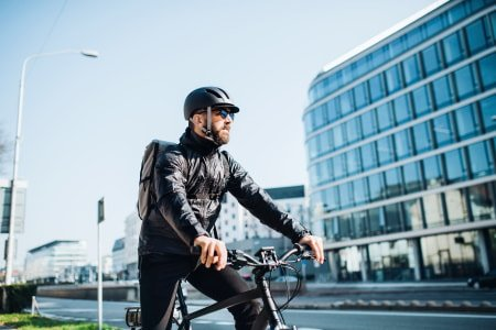 Electric bike rider wearing a helmet and jacket for cold weather conditions.
