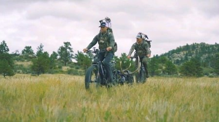 Hunters riding electric hunting bikes through a field.