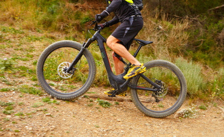 Climbing off-road inclines on an electric mountain bike.