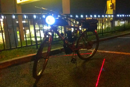 Motorized bicycle with headlight at night.