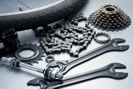Wrenches, bike chain, cassette, sprocket, and tire for a motorized bicycle.