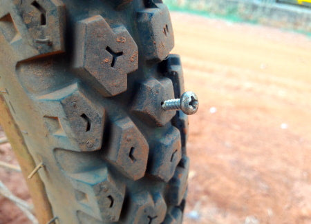 Motorized bicycle tire with a nail puncture.