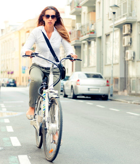 Businesswoman commuting through big city streets on an electric bike.