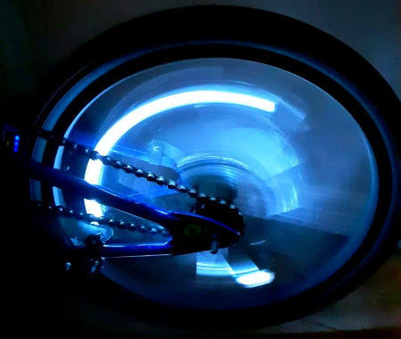 Bicycle wheel spinning with valve stem light.
