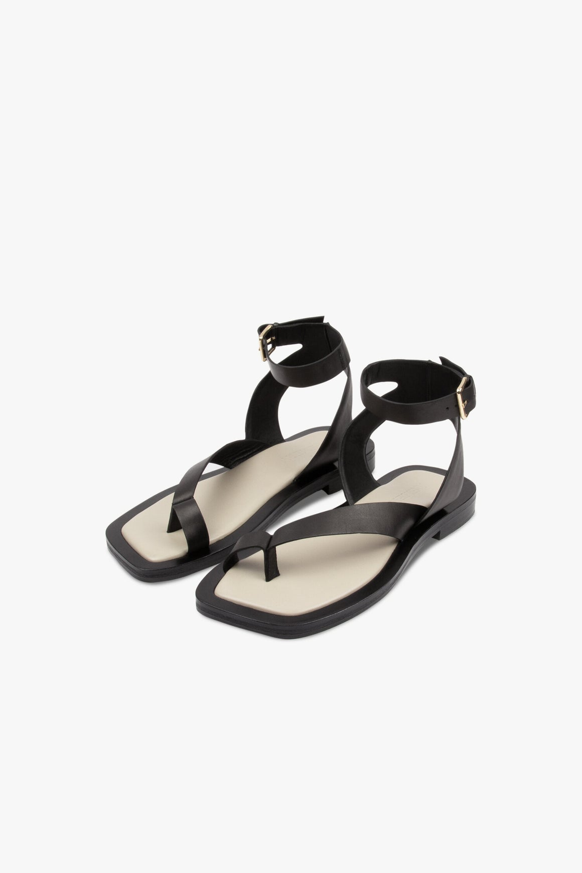 The Asher sandal features a toe hold at front with a sweeping strap across the foot up to a statement ankle strap. Finished with an elevated soft gold buckle.