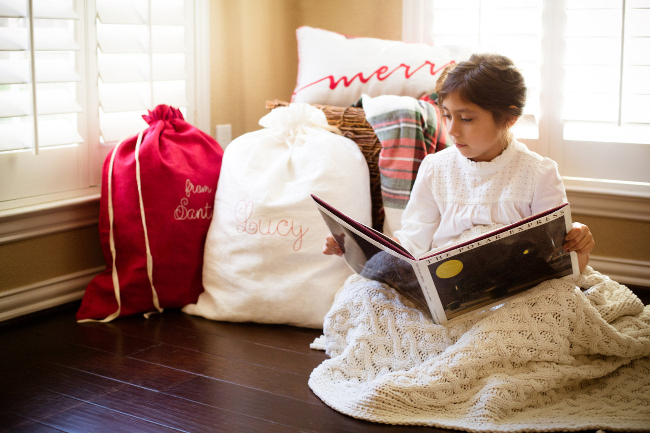 Girl Reading Polar Express on Christmas Eve with Personalised Santa Sacks in Background
