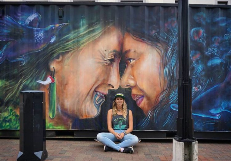 erika sitting in front of a mural she painted of two wahine toa maori